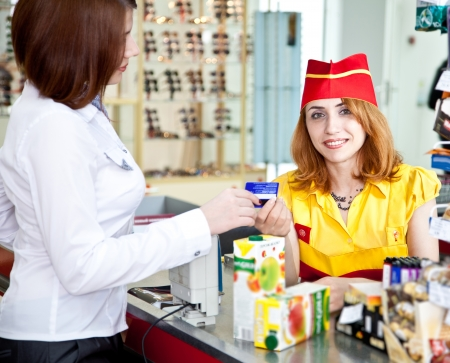 woman doing shopping in supermarket and paying by credit card Standard-Bild