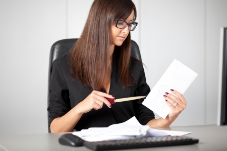 Portrait of a beautiful executive woman secretary at work while open a letter
