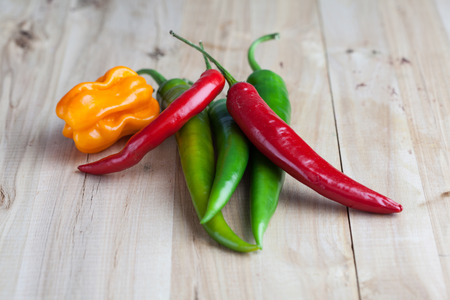 tex: mix of hottest peppers on wooden table