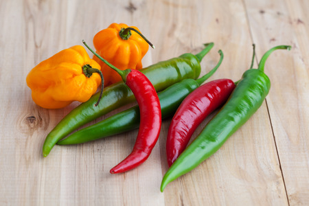 hottest: Mix of hottest peppers on wooden table