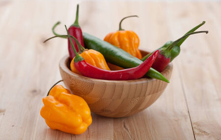 Mix of hottest peppers in wooden plate on table