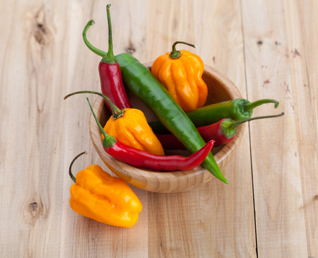 hottest: Mix of hottest peppers in wooden plate on table