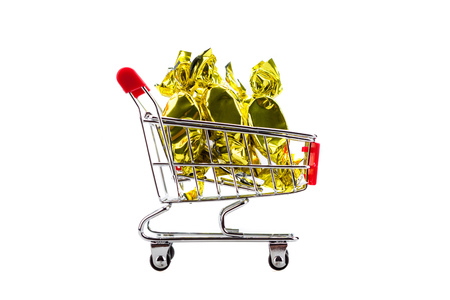 shopping binge: candy in wrappers in shopping cart, isolated on white background Stock Photo