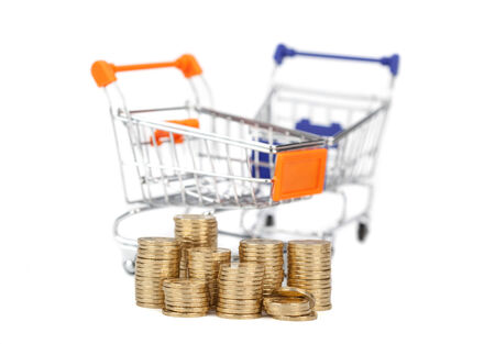 coins in a column on the background trolley from the supermarket. Focus on coins Stock Photo