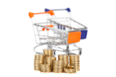 commercial activity: coins in a column on the background shopping carts Focus on coins