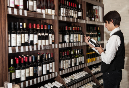 man looking at bottle of wine in supermarket. photo