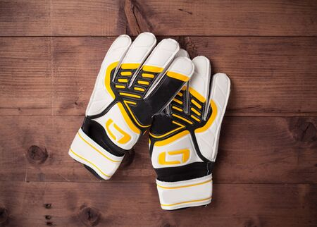 Gloves of the soccer goalkeeper on wooden table Stock Photo
