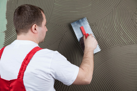 the working builder applies glue on a wall for a ceramic tile