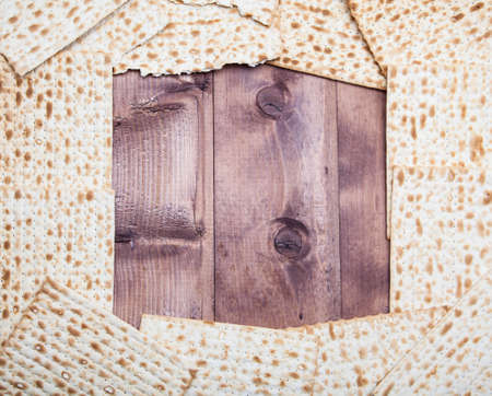 Jewish holiday Passover background. Matza on wooden table with copy space