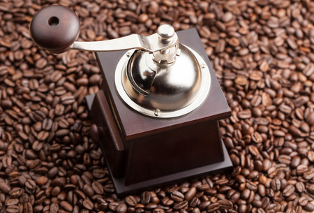 manual coffee grinder on a background of coffee beans