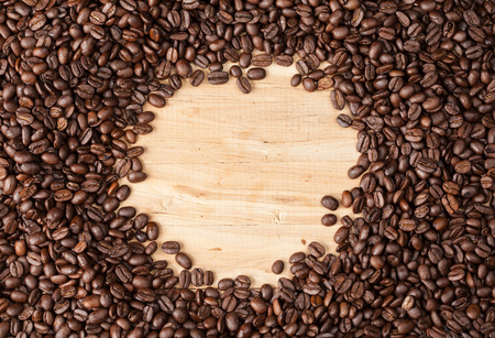 Circle frame of coffee beans on wooden table