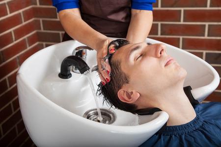 Barber at work. Man at barbershopHairdresser washing hair to young man. Standard-Bild