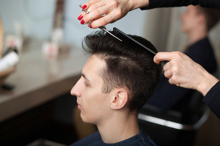 portrait of young man having haircut in barber shop. Hairdresser cutting mans hair with scissors Reklamní fotografie