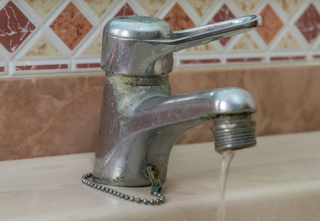 Water tap with limescale soiled bathroom Calcified faucet water flowing Standard-Bild