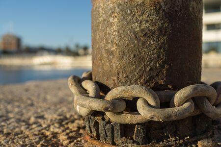 bollard: Old and rusty chains around a bollard macro detail