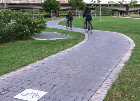 cycleway signposted a ground bikeway with two cyclists circling. Bike lane between trees in Jardin del Turia in Valencia Spain Imagens
