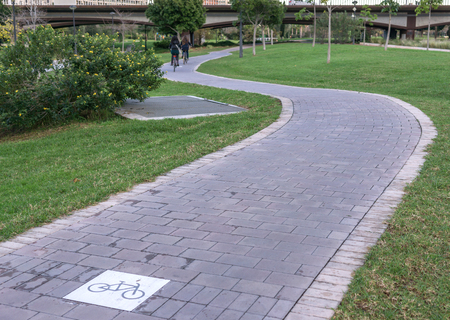 cycleway signposted a ground bikeway with two cyclists circling at background. Bike lane between trees in Jardin del Turia in Valencia Spain Stock Photo