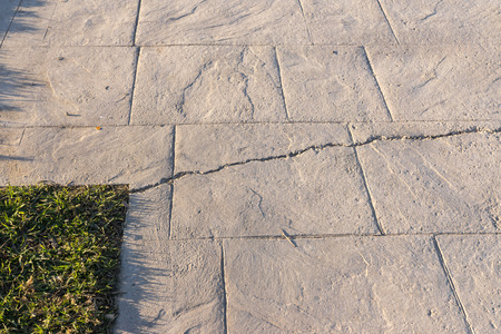 Deep break on surfaces of stamped concrete pavement outdoor, appearance colors and textures of paving slate stone tile on cement, flooring exterior decorative
