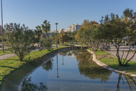 central european: Gardens in the old dry riverbed of the Turia river - reflection of trees in the artificial water channel and small bridge in the background. Valencia, Spain,