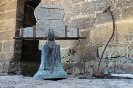 Original bronze rusty bells with its counterweight yoke and hammer. Bell tower on the church Late Gothic building of San Esteban de la Huerta built in the village of Loarre Aragon Huesca Spain.