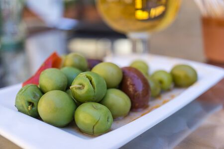 forefront: Marinated olives with herbs and spices in a small plate on the tapas bar table a typical Spanish black and green split olive. In the background a blurred beer Stock Photo