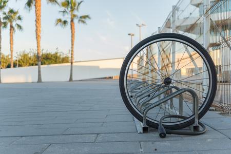 Une roue de vélo endommagée est tout ce qui reste d'une bicyclette enchaînée sur un support de vélo, une seule roue de bicyclette dans la rue en raison du vol, vélo volé, roue de vélo enchaînée, roue avant verrouillée Banque d'images - 75541432