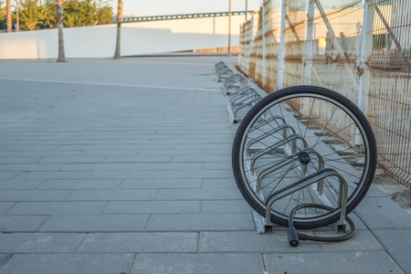 A damaged bike wheel is all that is left of a bicycle chained to a bike stand, a single bicycle wheel on the street due to stealing, Stolen bicycle, Chained bicycle wheel, front wheel locked Stock Photo