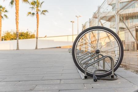 Bicicleta robada, rueda de bicicleta delantera encadenada bloqueada. Una rueda de bicicleta dañada es todo lo que queda, una sola rueda de bicicleta en la calle debido al robo.