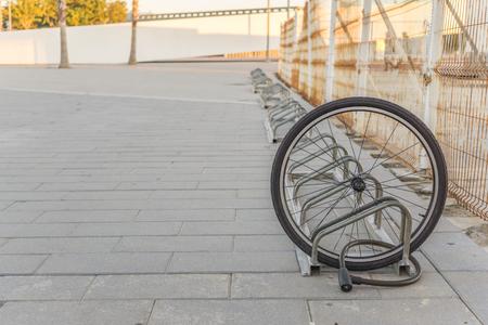 Gestohlenes Fahrrad, Chained Vorderradrad verriegelt. Ein beschädigtes Fahrradrad ist alles, was übrig bleibt, ein einziges Fahrradrad auf der Straße wegen des Diebstahls.