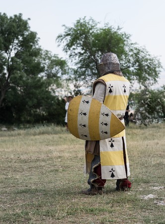 a war historian: Medieval knight ready for battle, reenactment with costumed characters and medieval armor with chainmail, helmet swords and shields. Medieval demonstration and recreation