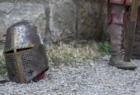 a war historian: Helmet of a medieval knight on the ground, in the background feet with ancient footwear