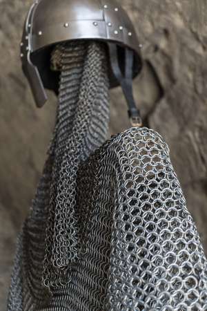 a war historian: Helmet, chainmail, sword and shields of a medieval armor knight ready for battle Stock Photo