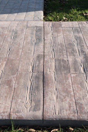 stamped concrete pavement outdoor with expansion joint at middle, Wooden slats pattern, flooring exterior, decorative texture of cement paving with streaks of wood