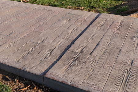 stamped concrete pavement outdoor with expansion joint working, Wooden slats pattern, flooring exterior, decorative texture of cement paving with streaks of wood Stock Photo