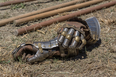 a war historian: Detail of gloves as part of a metallic armor, on a reenactment with costumed characters and medieval armor with chainmail, helmet swords and shields. Medieval demonstration and recreation