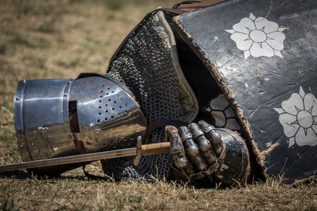 a war historian: Medieval knight fallen in battle, on a reenactment with costumed characters and medieval armor with chainmail, helmet swords and shields. Medieval demonstration and recreation Stock Photo