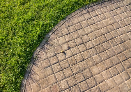 Stamped concrete pavement cobblestones pattern, decorative appearance colors and textures of paving cobblestones tile on cement flooring in a park with green lawn