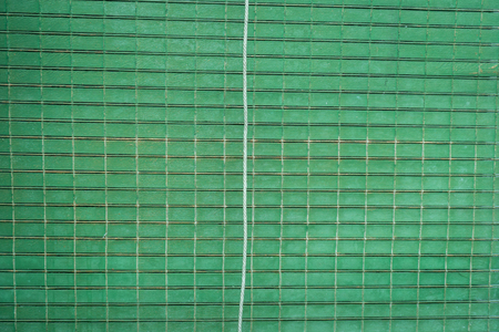 old lattice blinds painted green, planks of wood joined by ropes