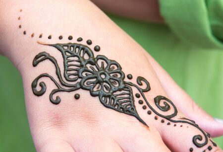 Henna tattoo on a hand, floral motif drawing. henna being applied to hand, freshly applied, still fresh