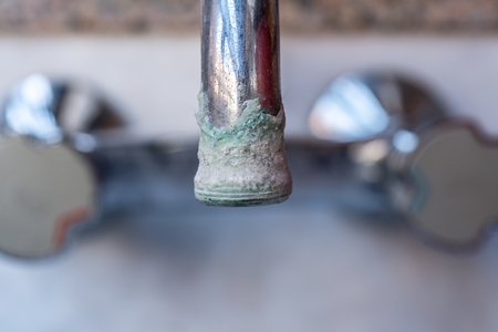 faucet with lime deposit calcified Calcification of a faucet in closeup Stock Photo