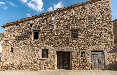 Old facade with stone cladding house, old barn in a village in spain Banque d'images - 121436910