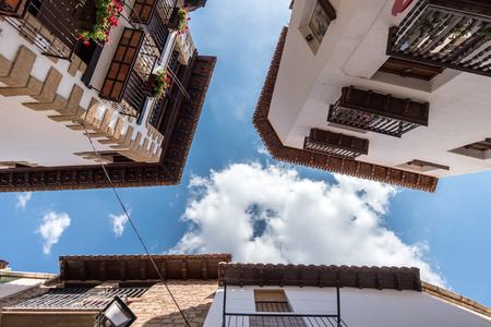 Wooden eaves of houses nearby in an old village of Spain, carved wood carving low angle shooting blue sky and clouds views, traditional architecture building