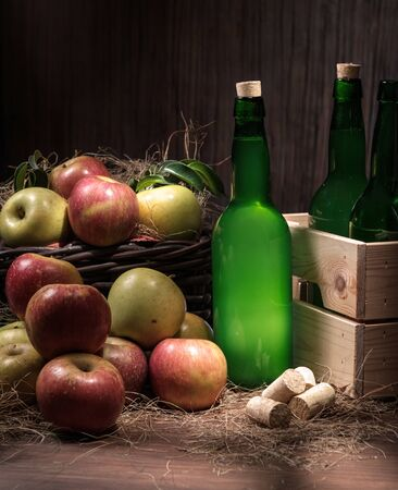 Asturian cider bottles wooden crate with many red and green apples at wicker basket over wooden background