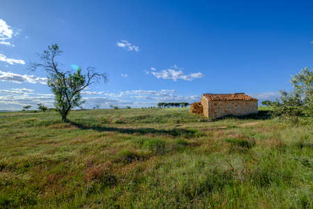 rustic rural house green field of nature blue sky, remote unpopulated site