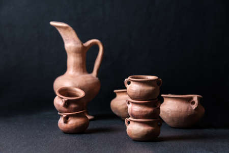 clay pots jug small mud vessel still life isolated on chiaroscuro black background