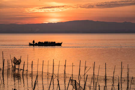 Albufera Sunset tourist ride boat orange sky at lake Natural Park Valencia Spain, traditional fishing nets in the water Standard-Bild