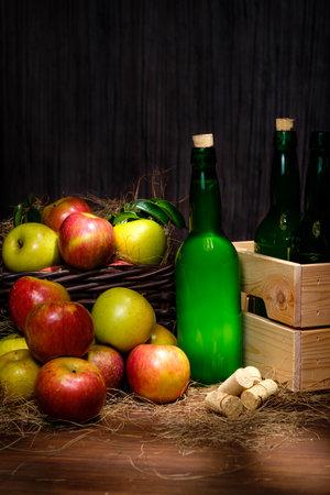 Asturian cider bottles many red and green apples at basket over wooden background