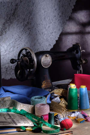 Old tailors workshop with sewing machine, threads, pins and fabrics, traditional vintage Standard-Bild