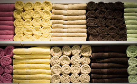 fabric roll: Colorful towels with wicker basket on shelf of rack background
