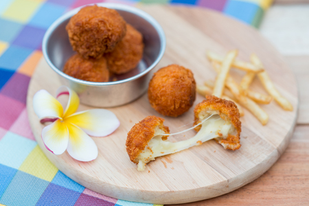 Deep fried cheese ball and french fries on wood dish Stock Photo
